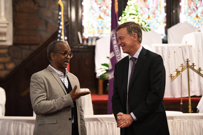 Former Colorado Gov. John Hickenlooper discusses gun control and death penalty issues with Anthony Thompson on Saturday, April 6, 2019, in Charleston, S. (AP Photo/Meg Kinnard)
