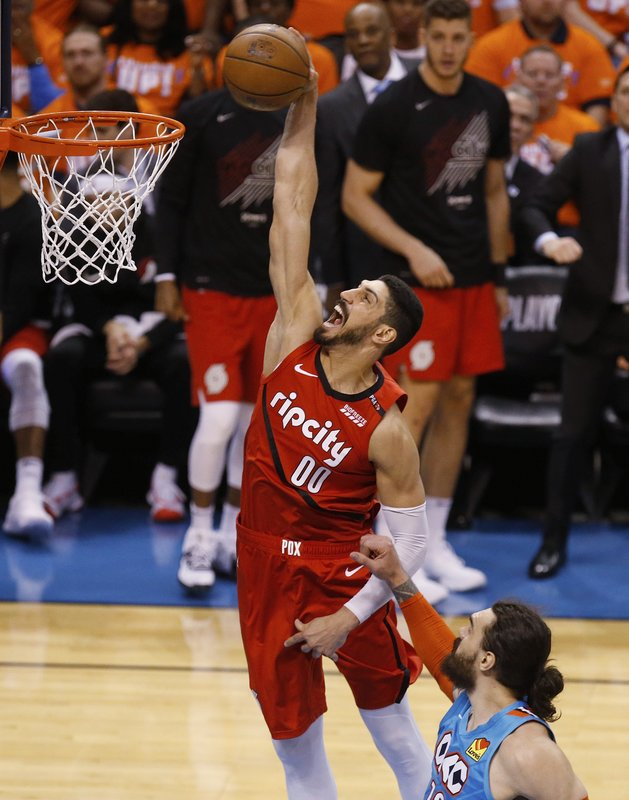 Portland Trail Blazers center Enes Kanter (00) dunks in front of Oklahoma City Thunder center Steven Adams, right, in the second half of Game 3 of an NBA basketball first-round playoff series Friday, April 19, 2019, in Oklahoma City. (AP Photo/Sue Ogrocki)