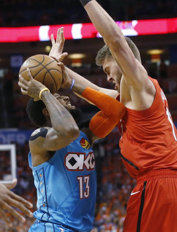 Oklahoma City Thunder forward Paul George (13) is fouled by Portland Trail Blazers forward Meyers Leonard, right, in the first half of Game 3 of an NBA basketball first-round playoff series Friday, April 19, 2019, in Oklahoma City. (AP Photo/Sue Ogrocki)