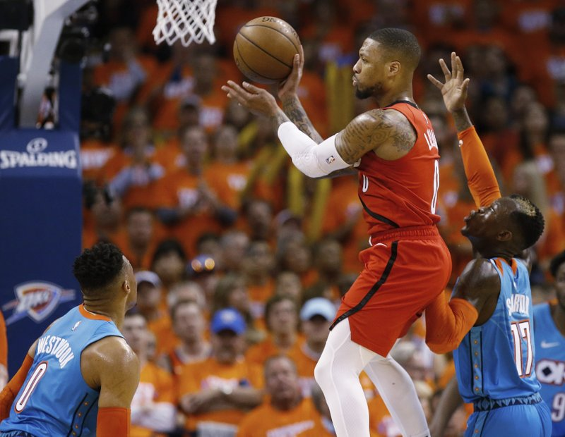 Portland Trail Blazers guard Damian Lillard, center, passes between Oklahoma City Thunder guard Russell Westbrook, left, and guard Dennis Schroder (17) in the first half of Game 3 of an NBA basketball first-round playoff series Friday, April 19, 2019, in Oklahoma City. (AP Photo/Sue Ogrocki)