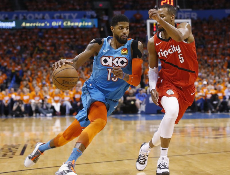 Oklahoma City Thunder forward Paul George (13) drives around Portland Trail Blazers guard Rodney Hood (5) in the first half of Game 3 of an NBA basketball first-round playoff series Friday, April 19, 2019, in Oklahoma City. (AP Photo/Sue Ogrocki)