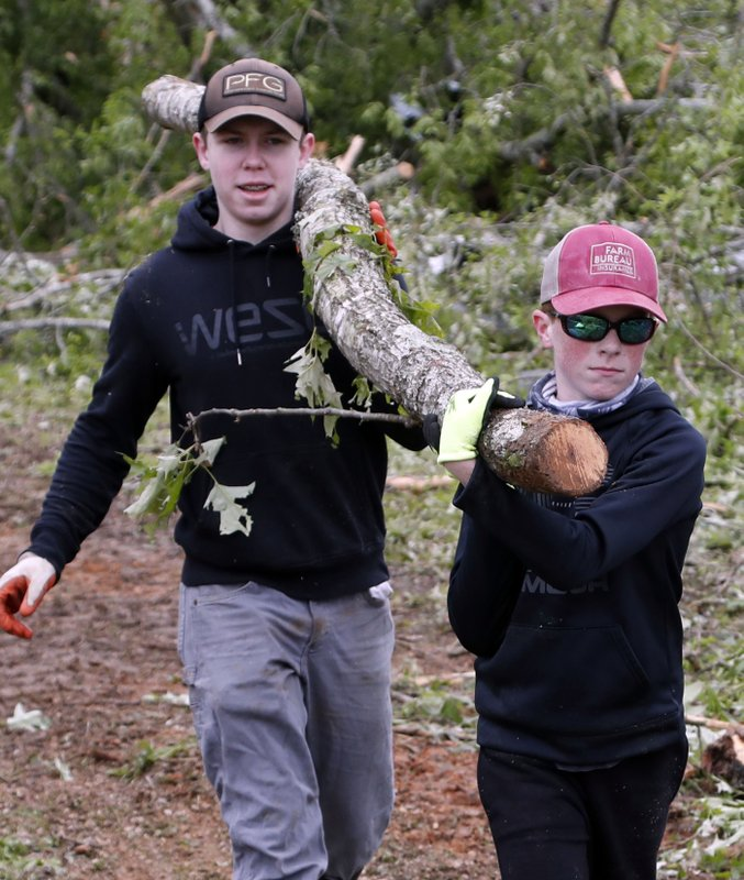Justus Harvey, 16, left, and his friend Gage Lee, 13, both of Forest, Miss., work in tandem to remove a branch Friday, April 19, 2019, in Morton, Miss. (AP Photo/Rogelio V. Solis)