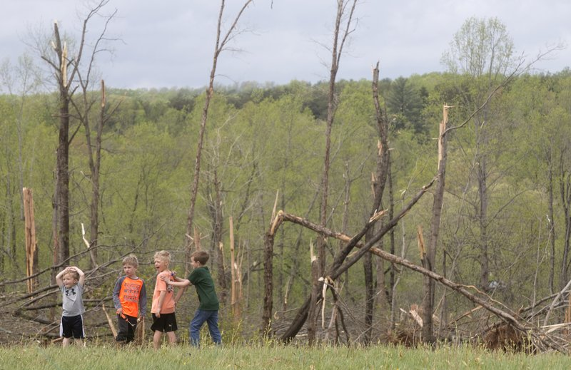 Damaged trees and children frame the property where Delores Anderson's house on Windy Ridge Road in Franklin County was leveled by a tornado Friday, April 19, 2019. (Heather Rousseau/The Roanoke Times via AP)