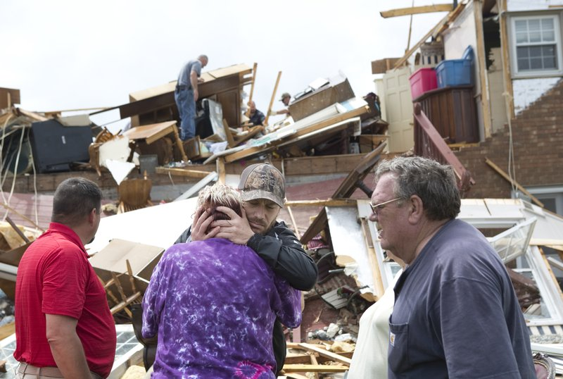 Delores Anderson, 63, center left, looks toward the wreckage of her house while comforted by friends and neighbors who came to support and help pull belongings from her home after it was destroyed by a tornado Friday, April 19, 2019, in Franklin County, Va. (Heather Rousseau/The Roanoke Times via AP)