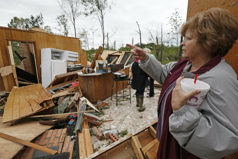 Freda Jenkins looks around the remains of a friend's possible tornado damaged home Friday, April 19, 2019, in Morton, Miss. (AP Photo/Rogelio V. Solis)