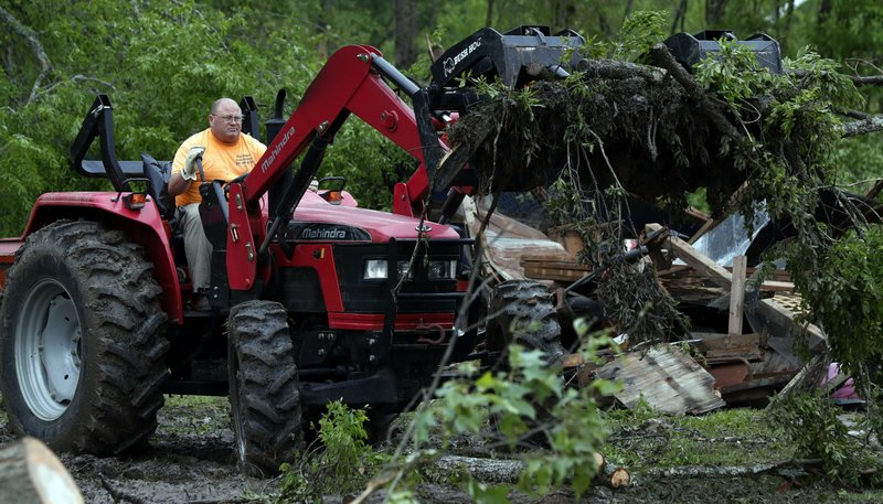 A farm tractor is used to remove debris from a tornado damaged home, Friday, April 19, 2019, in Morton, Miss. (AP Photo/Rogelio V. Solis)