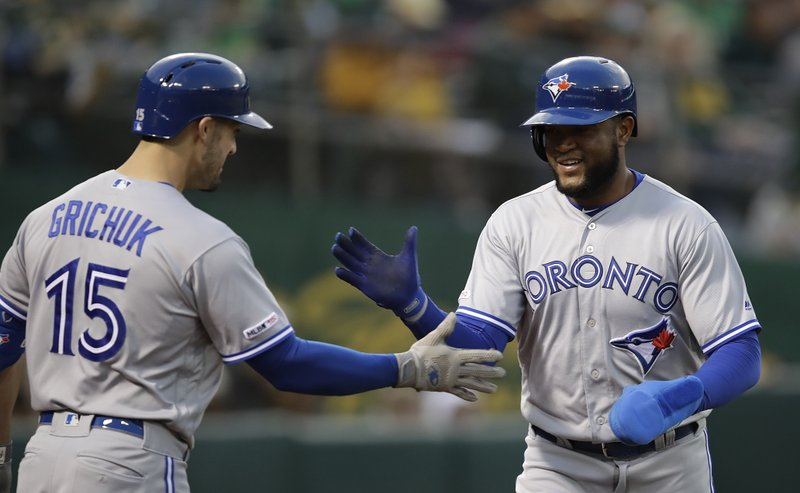 Toronto Blue Jays' Socrates Brito, right, is congratulated by Randal Grichuk (15) after scoring against the  Oakland Athletics in the second inning of a baseball game Friday, April 19, 2019, in Oakland, Calif. (AP Photo/Ben Margot)