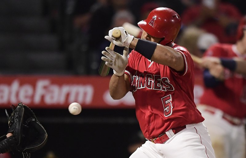 Los Angeles Angels' Albert Pujols is hit by a pitch during the eighth inning of the team's baseball game against the Seattle Mariners on Friday, April 19, 2019, in Anaheim, Calif. (AP Photo/Mark J. Terrill)