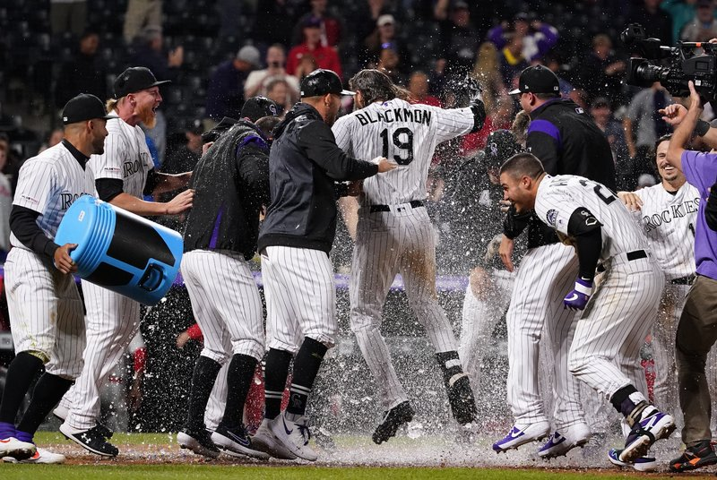 Colorado Rockies' Charlie Blackmon is congratulated for his walk-off home run against the Philadelphia Phillies during the 12th inning of a baseball game Friday, April 19, 2019, in Denver. (AP Photo/Jack Dempsey)