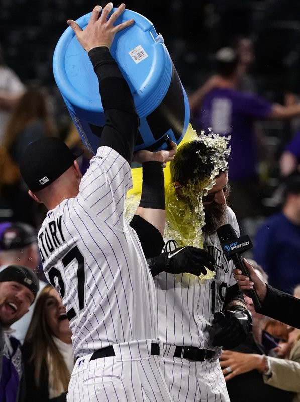 Colorado Rockies' Charlie Blackmon is doused by Trevor Story after Blackmon's walk-off home run against the Philadelphia Phillies during the 12th inning of a baseball game Friday, April 19, 2019, in Denver. (AP Photo/Jack Dempsey)