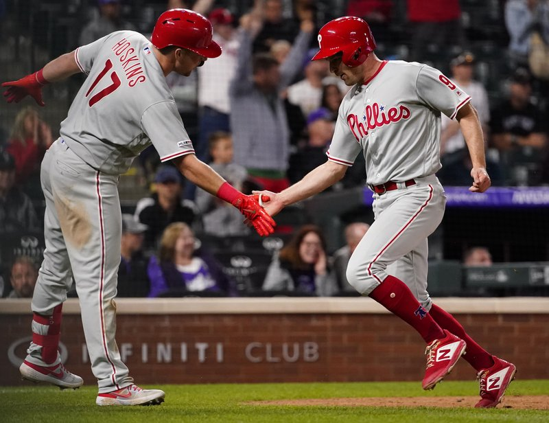 Philadelphia Phillies' Phil Gosselin (9) celebrates with Rhys Hoskins (17) after scoring on Bryce Harper's double against the Colorado Rockies during the 12th inning of a baseball game Friday, April 19, 2019, in Denver. (AP Photo/Jack Dempsey)