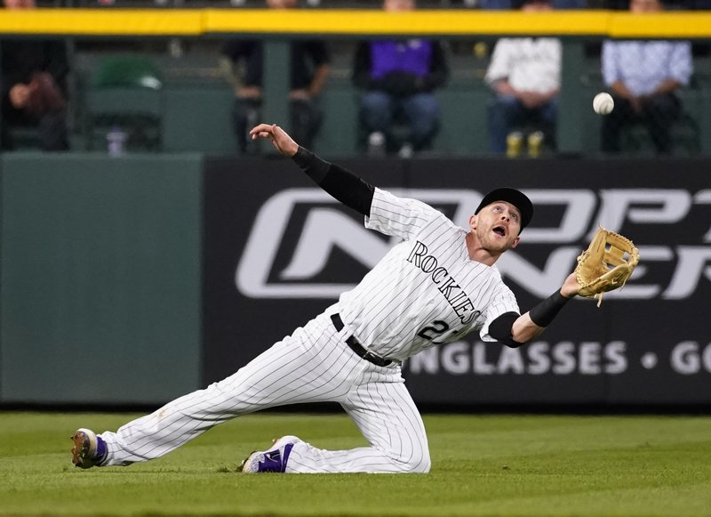 Colorado Rockies shortstop Trevor Story (27) dives to catch a fly ball off the bat of Philadelphia Phillies' Maikel Franco during the 10th inning of a baseball game Friday, April 19, 2019, in Denver. (AP Photo/Jack Dempsey)