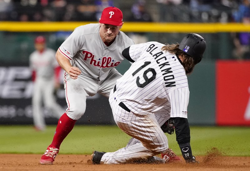 Philadelphia Phillies shortstop Phil Gosselin, left, tags out Colorado Rockies' Charlie Blackmon (19) on an attempted steal at second during the seventh inning of a baseball game Friday, April 19, 2019, in Denver. (AP Photo/Jack Dempsey)