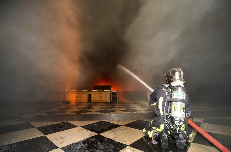 In this photo provided by the Paris Fire Brigade, firefighters spray water inside the Notre Dame cathedral, Monday April 15, 2019. (Benoit Moser/BSPP via AP)