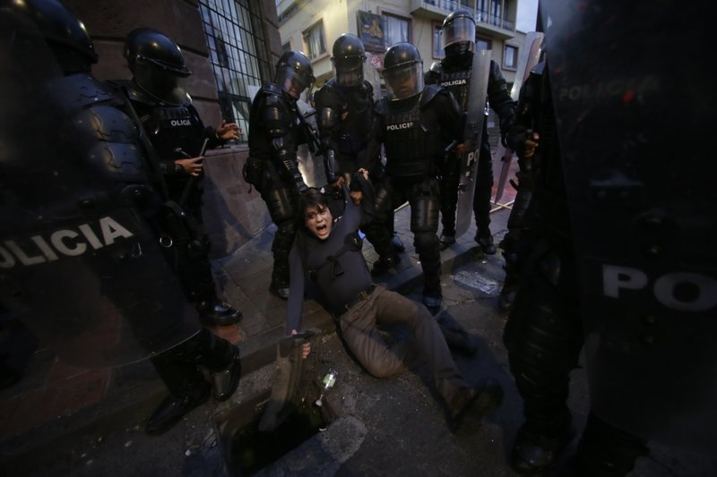A man is detained by police blocking protesters from advancing closer to the presidential palace in Quito, Ecuador, Tuesday, April 16, 2019. (AP Photo/Dolores Ochoa)