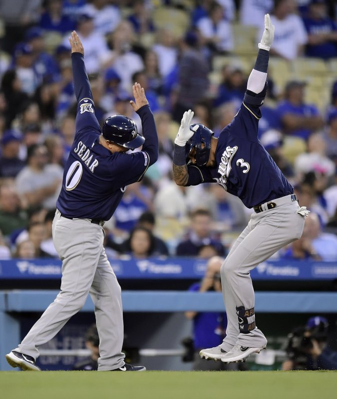 Milwaukee Brewers' Orlando Arcia, right, celebrates with third base coach Ed Sedar as he rounds third after hitting a solo home run during the fourth inning of the team's baseball game against the Los Angeles Dodgers on Saturday, April 13, 2019, in Los Angeles. (AP Photo/Mark J. Terrill)