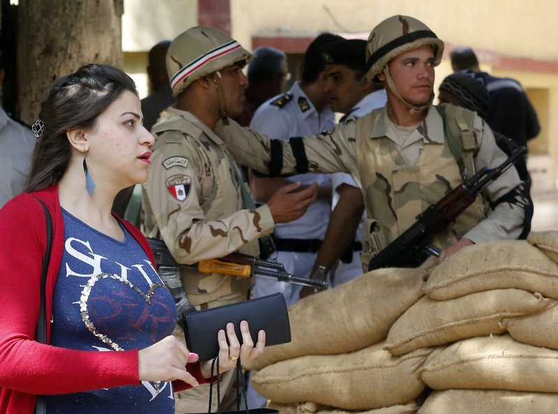 A voter leaves a polling station guarded by soldiers after she casting her ballot on constitutional amendments during the first day of three-day voting in Cairo, Egypt, Saturday, April 20, 2019. (AP Photo/Amr Nabil)