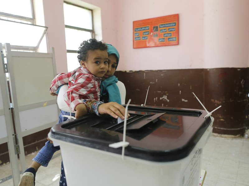 A voters carries her son as she casts her ballot on constitutional amendments during the first day of three-day voting at polling station in Cairo, Egypt, Saturday, April 20, 2019. (AP Photo/Amr Nabil)