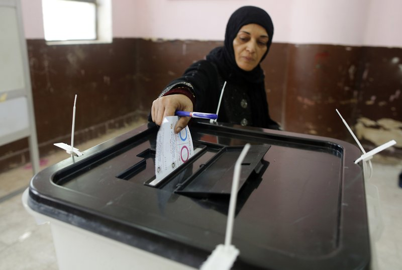 A voter casts her ballot on constitutional amendments during the first day of three-day voting at a polling station in Cairo, Egypt, Saturday, April 20, 2019. (AP Photo/Amr Nabil)