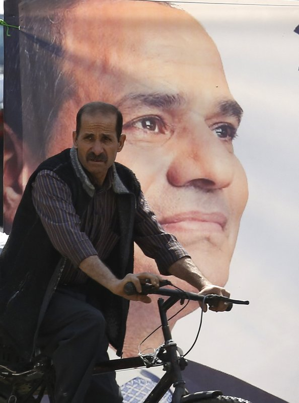 A voter rides his bicycle past a poster supporting Egyptian President Abdel-Fattah el-Sissi near a polling station in Cairo, Egypt, Saturday, April 20, 2019. (AP Photo/Amr Nabil)