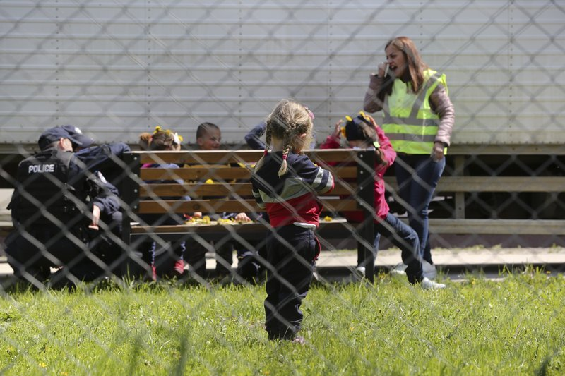 Police officers play with a group of children at a detention center where authorities have brought back from Syria 110 Kosovar citizens, mostly women and children in the village of Vranidol on Sunday, April 20, 2019. (AP Photo/Visar Kryeziu)