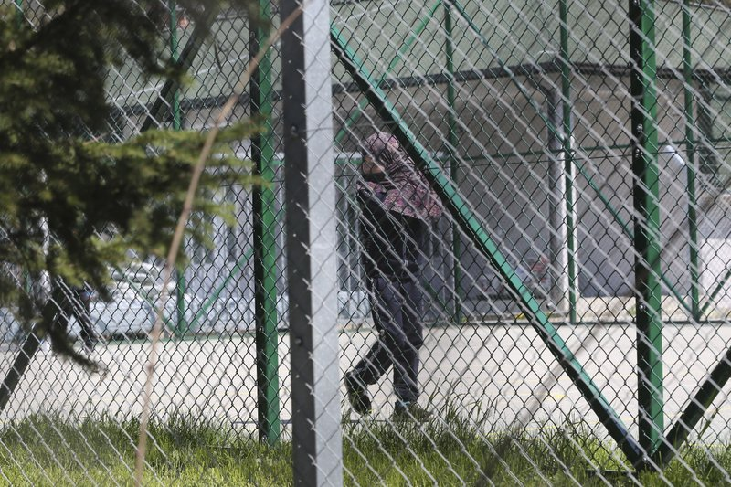 A girl walks inside a detention center where authorities brought back from Syria 110 Kosovar citizens, mostly women and children in the village of Vranidol on Sunday, April 20, 2019. (AP Photo/Visar Kryeziu)