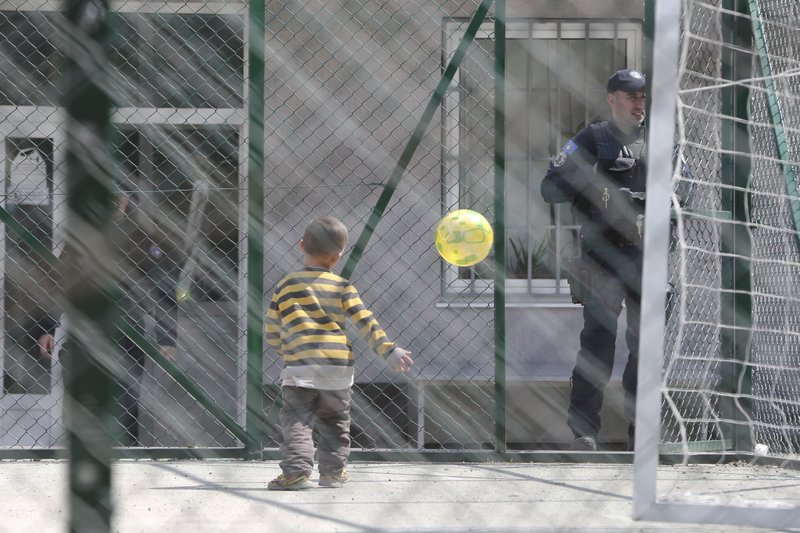 A child plays with a ball near a police officer at a detention center where authorities have brought back from Syria 110 Kosovar citizens, mostly women and children in the village of Vranidol on Sunday, April 20, 2019. (AP Photo/Visar Kryeziu)
