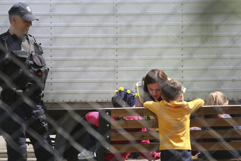 A police officer plays with a group of children inside a detention center where authorities have brought back from Syria 110 Kosovar citizens, mostly women and children in the village of Vranidol on Sunday, April 20, 2019. (AP Photo/Visar Kryeziu)