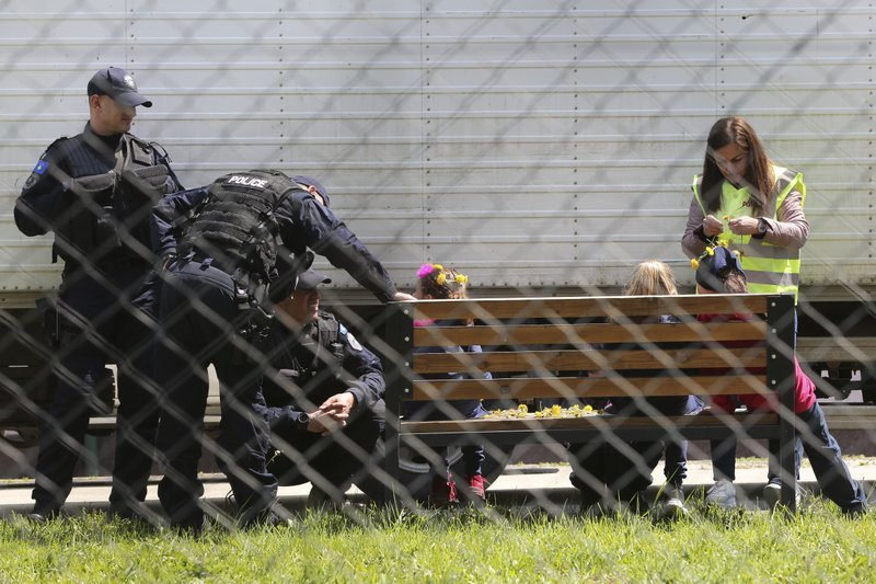 A police officer decorates a girl with dandelions as she plays with a group of children at a detention center where authorities have brought back from Syria 110 Kosovar citizens, mostly women and children in the village of Vranidol on Sunday, April 20, 2019. (AP Photo/Visar Kryeziu)