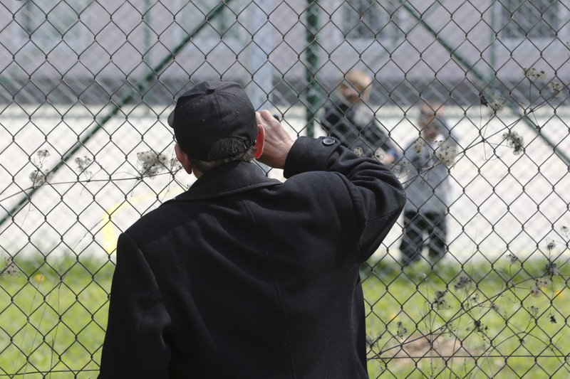 Hajdar Selimovic calls to his nephew Ismail behind a fence at a detention center where authorities have brought back from Syria 110 Kosovar citizens, mostly women and children in the village of Vranidol on Sunday, April 20, 2019. (AP Photo/Visar Kryeziu)