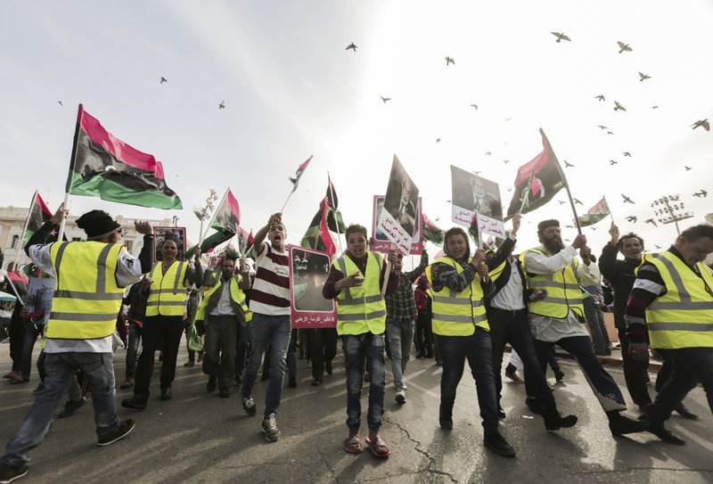 Protesters wear yellow vests at a protest in Tripoli, Libya as they chant slogans against Libya's Field Marshal Khalifa Hifter, who is leading an offensive to take over the capital of Tripoli, Friday, April 19, 2019. (AP Photo/Hazem Ahmed)