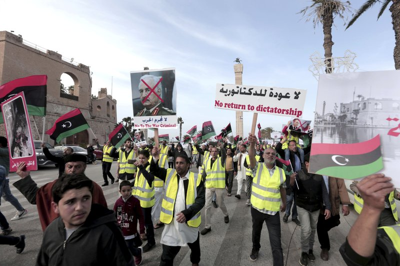 Protesters wear yellow vests at a protest in Tripoli, Libya as they wave national flags and chant slogans against Libya's Field Marshal Khalifa Hifter, who is leading an offensive to take over the capital of Tripoli, Friday, April 19, 2019. (AP Photo/Hazem Ahmed)