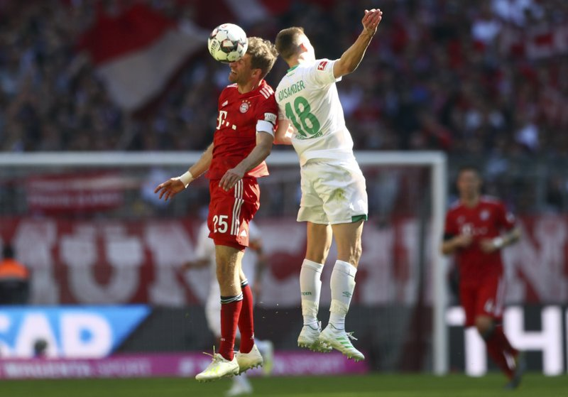 Bayern forward Thomas Mueller, left jumps for a header with Bremen's defender Niklas Moisander during the German Bundesliga soccer match between Bayern Munich and Werder Bremen at the Allianz Arena in Munich, Germany, Saturday, April 20, 2019. (AP Photo/Matthias Schrader)