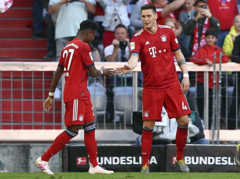 Bayern defender Niklas Suele, right, celebrates with Bayern defender David Alaba after scoring his side's opening goal during the German Bundesliga soccer match between Bayern Munich and Werder Bremen at the Allianz Arena in Munich, Germany, Saturday, April 20, 2019. (AP Photo/Matthias Schrader)