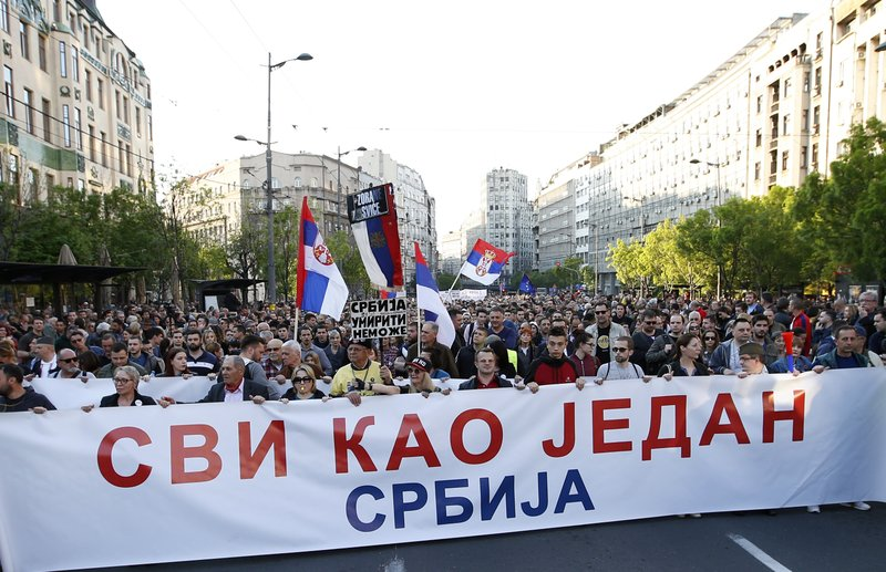 People hold a banner that reads: ''All as one - Serbia'' during a protest march against president Aleksandar Vucic in Belgrade, Serbia, Saturday, April 20, 2019. (AP Photo/Darko Vojinovic)