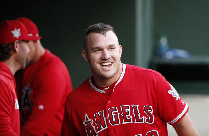 Los Angeles Angels designated hitter Mike Trout smiles in the dugout after he scored on a home run by Brian Goodwin against the Texas Rangers during the first inning of a baseball game Monday, April 15, 2019, in Arlington, Texas. (AP Photo/Michael Ainsworth)