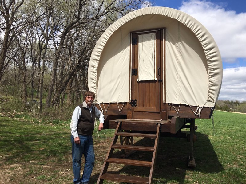 In this April, 11, 2019 photo, Dennis Steinman stands by the back door of one of his custom-built covered wagons outside his home in rural Douglas County, Kansas. (Kathy Hanks/Lawrence Journal-World)