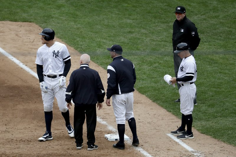New York Yankees' Aaron Judge, left, reacts while talking to a trainer and bench coach Josh Bard, center, after hitting a single to right field during the sixth inning of a baseball game against the Kansas City Royals, Saturday, April 20, 2019, in New York. (AP Photo/Julio Cortez)