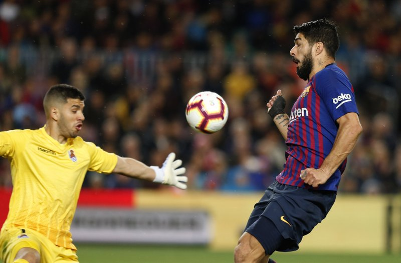 Barcelona forward Luis Suarez fights for the ball against Real Sociedad's goalkeeper Geronimo Rulli during a Spanish La Liga soccer match between FC Barcelona and Real Sociedad at the Camp Nou stadium in Barcelona, Spain, Saturday, April 20, 2019. (AP Photo/Joan Monfort)