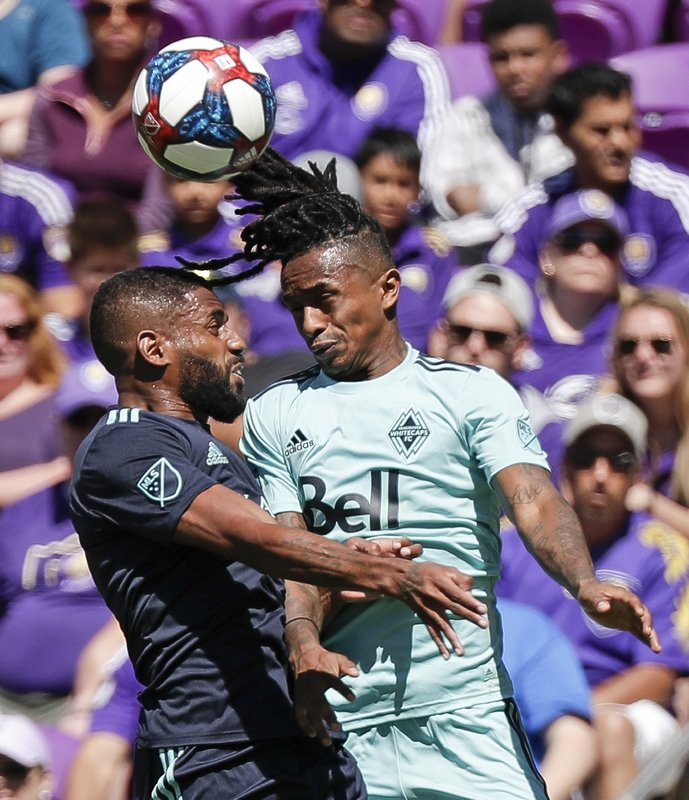 Orlando City's Ruan, left, and Vancouver Whitecaps' Yordi Reyna go up for a header to gain possession of the ball during the first half of an MLS soccer match, Saturday, April 20, 2019, in Orlando, Fla. (AP Photo/John Raoux)