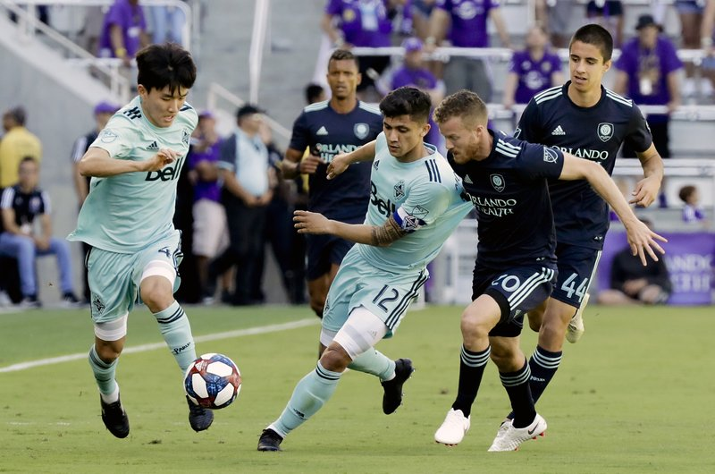 Vancouver Whitecaps' Hwang In-Beom, left, with the help of teammate Fredy Montero (12) moves the ball past Orlando City's Oriol Rosell during the first half of an MLS soccer match, Saturday, April 20, 2019, in Orlando, Fla. (AP Photo/John Raoux)