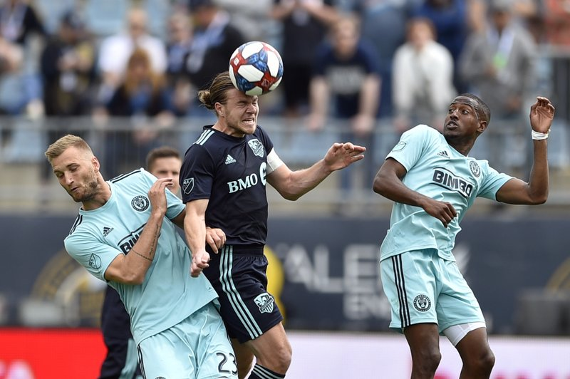 Montreal Impact's Samuel Piette, center, heads the ball past the defense of Philadelphia Union's Kacper Przybylko, left, and Fafa Picault during the second half of an MLS soccer match, Saturday, April 20, 2019, in Chester, Pa. (AP Photo/Derik Hamilton)