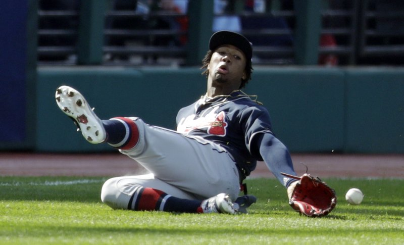 Atlanta Braves' Ronald Acuna Jr. dives for a ball hit by Cleveland Indians' Carlos Santana in the first inning during the first game of a baseball doubleheader, Saturday, April 20, 2019, in Cleveland. (AP Photo/Tony Dejak)