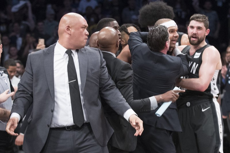 CORRECTS TO SECOND HALF NOT FIRST HALF - Brooklyn Nets head coach Kenny Atkinson, third from right, restrains Nets forward Jared Dudley, second from right, after Dudley got into a shoving match during the second half of Game 4 of a first-round NBA basketball playoff series against the Philadelphia 76ers, Saturday, April 20, 2019, in New York. (AP Photo/Mary Altaffer)