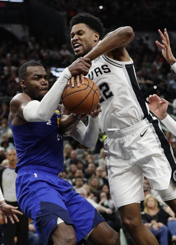 Denver Nuggets forward Paul Millsap, left, and San Antonio Spurs forward Rudy Gay, right, battle for control of the ball during the first half of Game 4 of an NBA basketball playoff series, in San Antonio, Saturday, April 20, 2019. (AP Photo/Eric Gay)