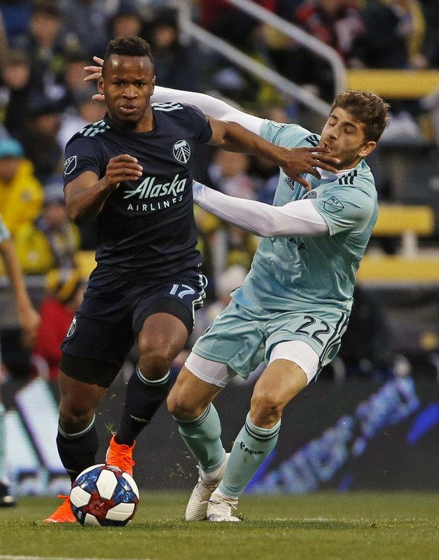 Columbus Crew defender Gaston Sauro (22) makes contact with Portland Timbers forward Jeremy Ebobisse (17) in the first half of an MLS soccer game in Columbus, Ohio, Saturday, April 20, 2019. (Eric Albrecht/The Columbus Dispatch via AP)