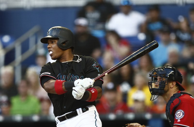 Miami Marlins' Starlin Castro (13) hits a double during the first inning of a baseball game against the Washington Nationals on Saturday, April 20, 2019, in Miami. (AP Photo/Brynn Anderson)