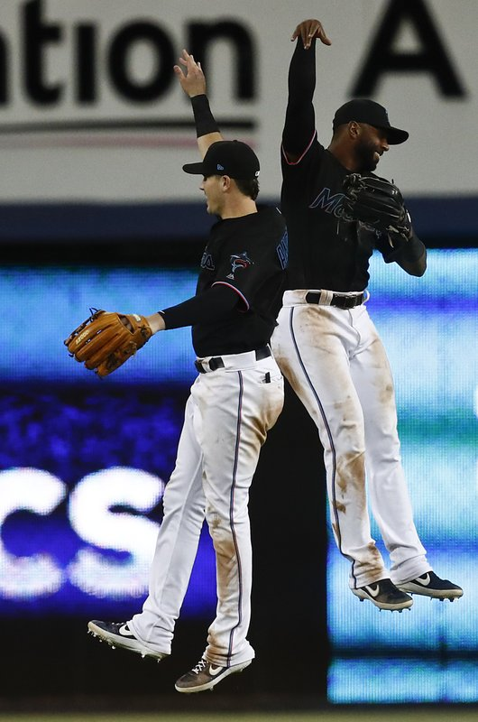 Miami Marlins third baseman Brian Anderson (15) and Miami Marlins right fielder Isaac Galloway (79) celebrate their win against the Washington Nationals after a baseball game on Saturday, April 20, 2019, in Miami. (AP Photo/Brynn Anderson)