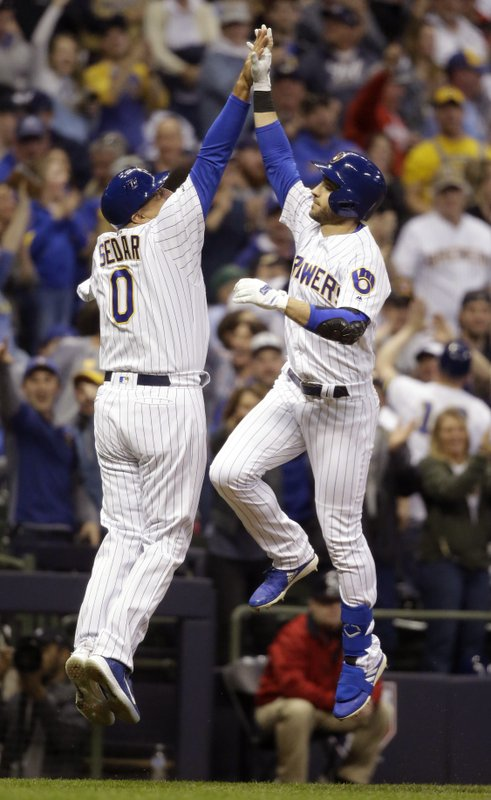 Milwaukee Brewers' Ryan Braun reacts with third base coach Ed Sedar after his three-run home run against the Los Angeles Dodgers during the seventh inning of a baseball game Saturday, April 20, 2019, in Milwaukee. (AP Photo/Jeffrey Phelps)