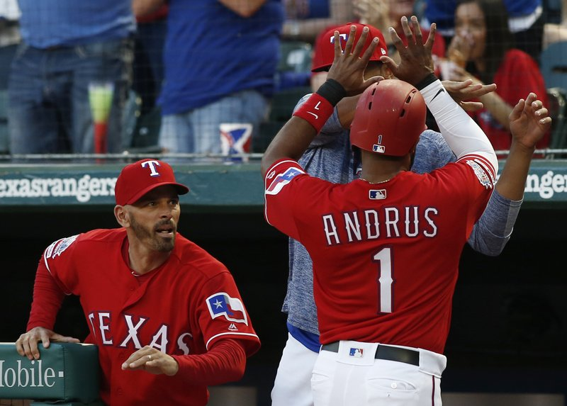 CORRECTS DATE - Texas Rangers manager Chris Woodward congratulates Elvis Andrus (1) after he scored against the Houston Astros during the first inning of a baseball game Saturday, April 20, 2019, in Arlington, Texas. (AP Photo/Mike Stone)